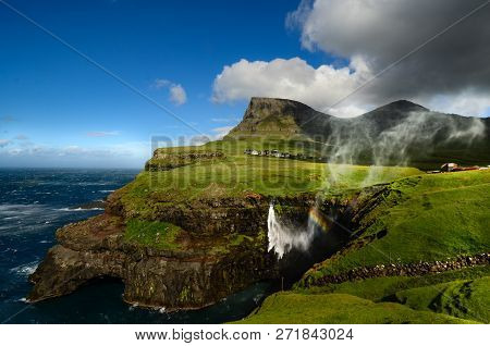 Waterfall With Rainbow In Front Ov A Little Village And Stunning Mountain Range