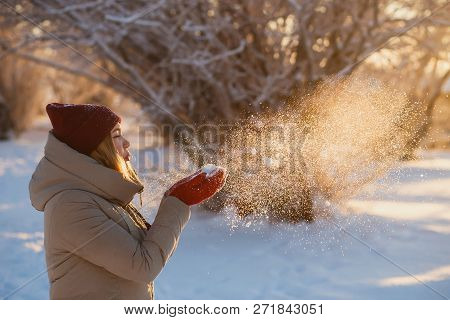 Winter Holiday, Fun And People Concept - Young Woman In Red Winter Hat Blowing Snow From Red Mittens