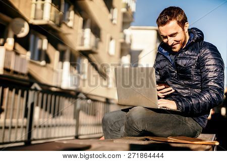 Man Wearing Autumn Jacket Working From Outdoor Office And Staying Connected With Technology, Texting