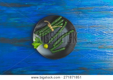 Kabanosy, Sausages Green With Wasabi Made Of Pork In Plate On A Dark Blue Wood Surface With Addition