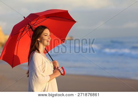 Happy Woman Holding Red Umbrella Contemplating The Ocean Walking On The Beach