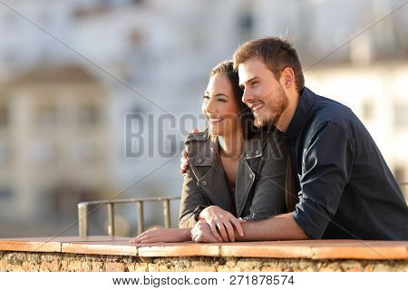 Happy Couple Contemplating Views From A Balcony At Sunset With A Town In The Background