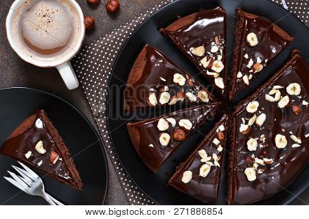 Chocolate Cake With Hot Chocolate Sauce And Fried Hazelnuts On A Dark, Concrete Background.