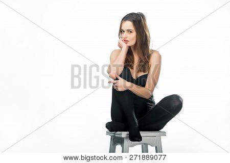 Young beautiful sexy woman posing sitting in black lingerie and tights on a chair over white background. Seductive woman with long dark hair sits in black hosiery. poster
