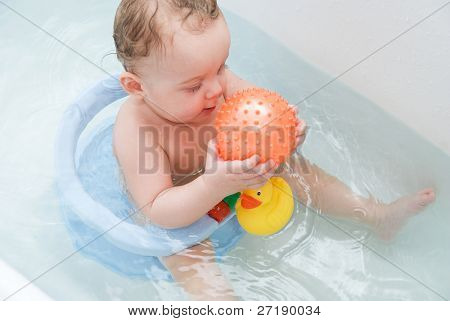 beauty baby boy in bath with rubber ball