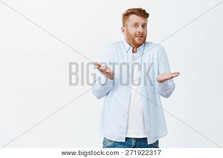 So What. Portrait Of Confused Unaware Good-looking Redhead Male With Bristle, Shrugging With Raised