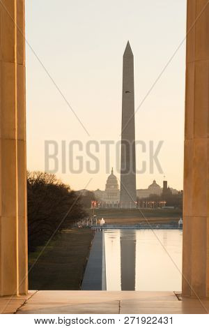 Washington Monument and Capitol as seen between columns of Lincoln Memorial at sunrise - Washington DC USA