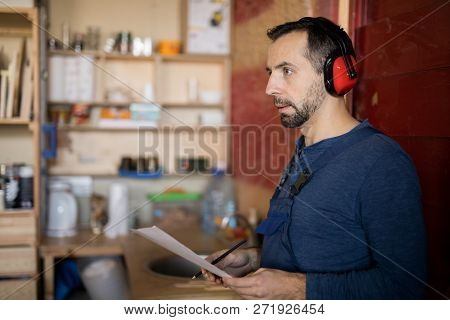 Side view portrait of mature bearded worker wearing noise-cancelling earphones working in joinery, copy space poster