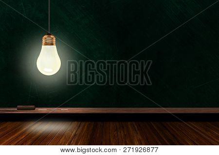Hanging And Illuminated Light Bulb In A Classroom With Background Chalk Board And Wooden Table And C