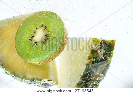 Slices Of Fresh Pineapple And Kiwi In Clear Clear Water.