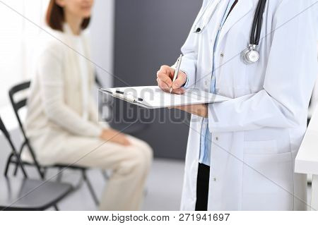 Doctor Woman Filling Up Medical Form While Standing Near Reception Desk At Clinic Or Emergency Hospi