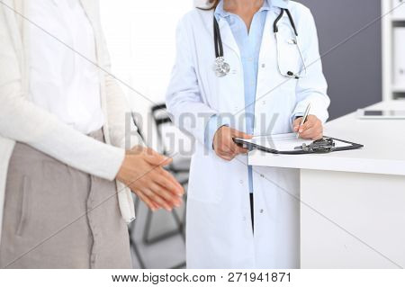 Unknown Doctor And  Female Patient  Discussing Something While Standing Near Reception Desk In Emerg