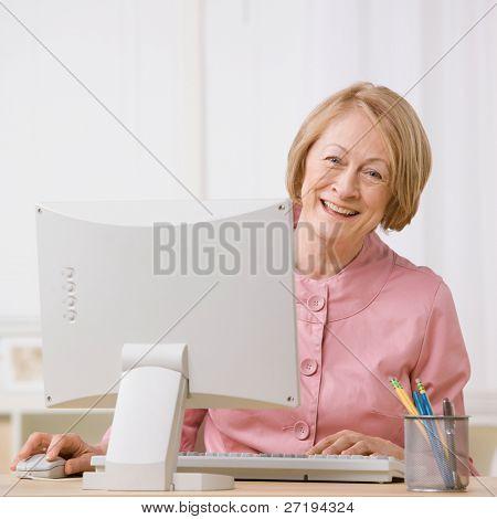 หญิงอาวุโสความสุขที่ทำงานบนคอมพิวเตอร์ที่โต๊ะ