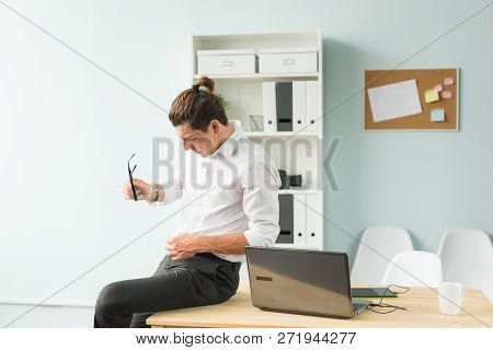 Business, Humor And People Concept - Young Man In White Shirt Sitting On Wooden Table