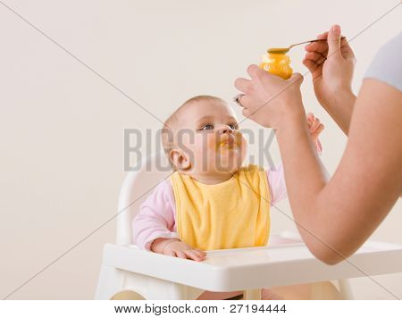 Studio shot of mother feeding hungry baby in highchair
