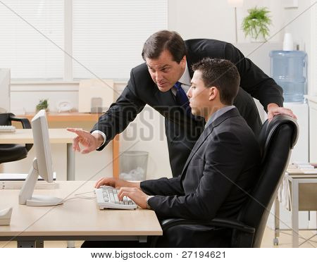 Supervisor gesturing and explaining work to young businessman at desk