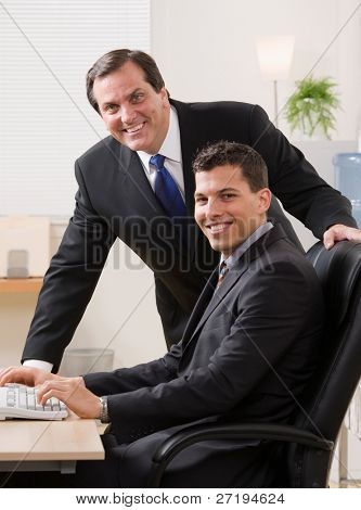 Confident businessmen smiling at desk in office