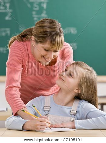 Teacher explaining homework to student in school classroom