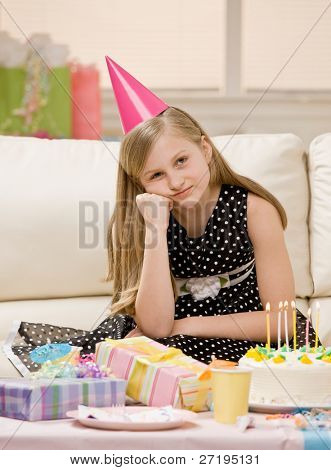 Unhappy and ungrateful girl in party hat sits with gifts and birthday cake at party
