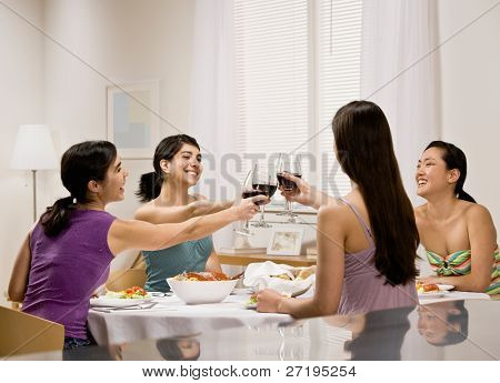 Friends toasting with red wine at dinner party
