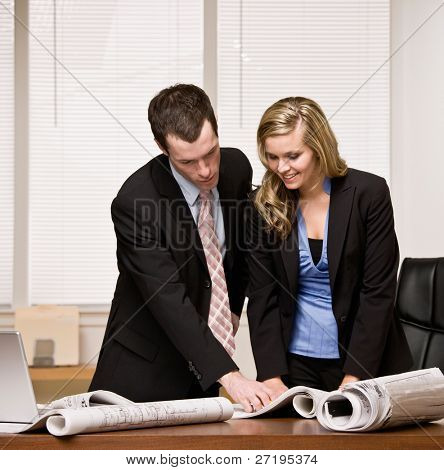 Architect co-workers review blueprints at desk