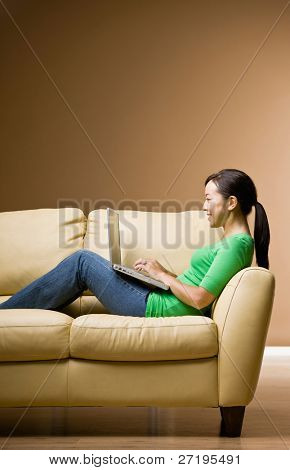 Woman relaxing on sofa in livingroom typing on laptop