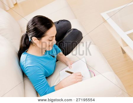 Relaxed woman laying on sofa in livingroom writing in diary