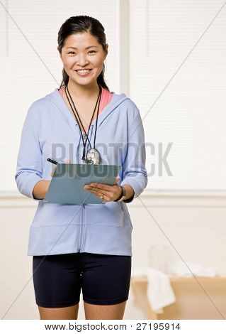 Confident personal trainer holds clipboard