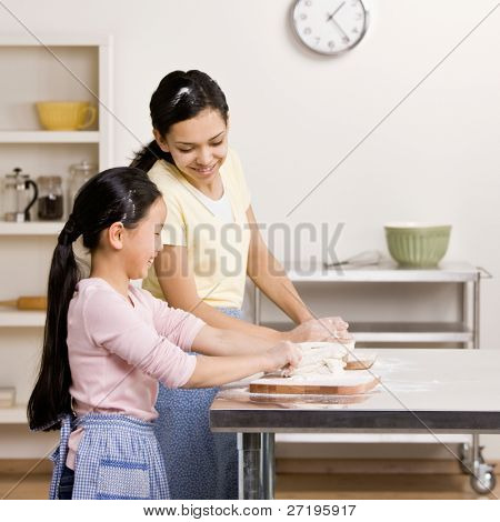 Teenager teaches sister how to knead dough in kitchen