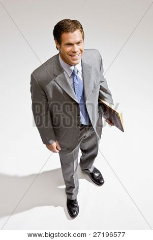 Confident businessman standing with notebook