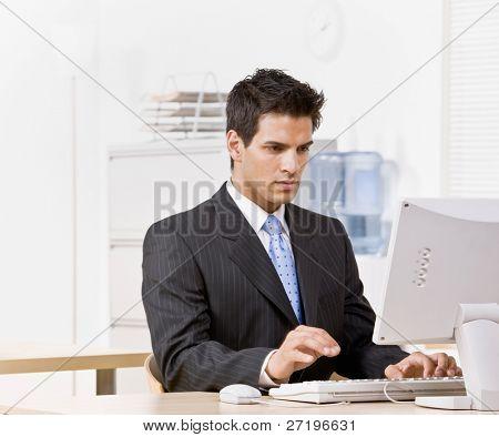 Empresario serio escribir en computadora