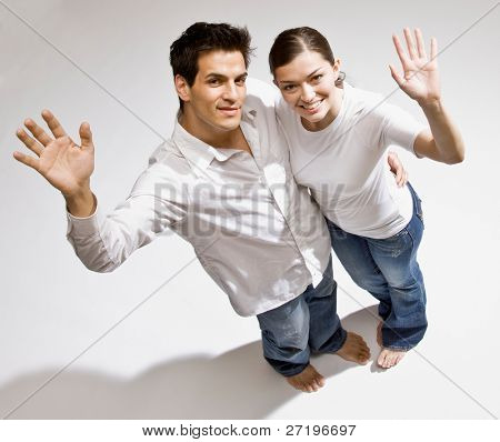 Happy barefoot couple waving a greeting