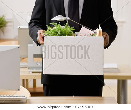 Fired businessman packing personal desk items in box