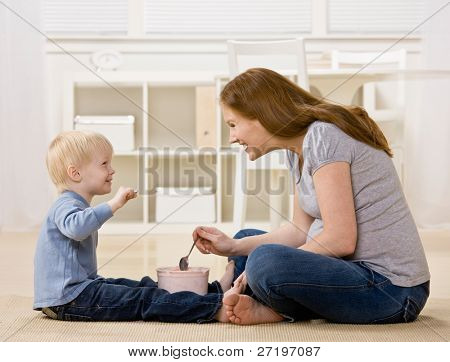 Happy son eats ice cream from tub with excited mother