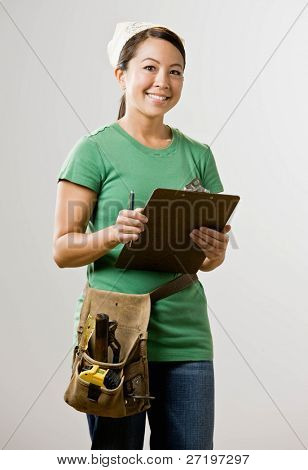 Self-sufficient woman with clipboard and tool belt