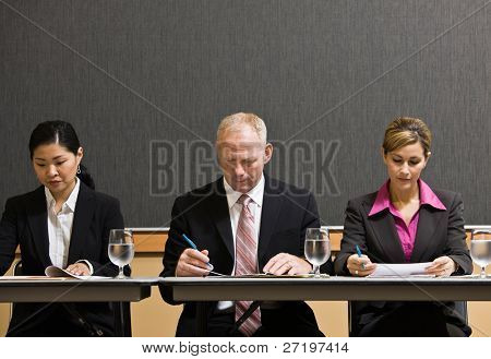 Busy co-workers meeting at table in conference room