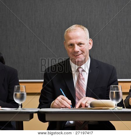 Mature businessman writing notes at table in conference room
