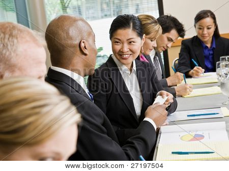 Businessman offering business card to female colleague in conference room