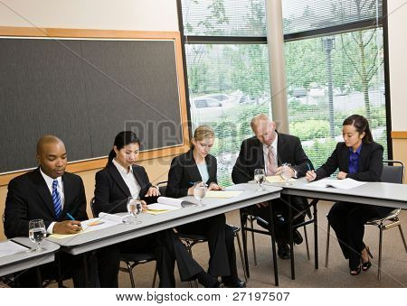 Multi-ethnic co-workers sitting around table in conference room