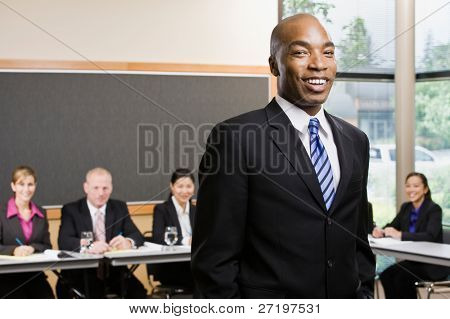 Confident African businessman standing in front of co-workers in conference room