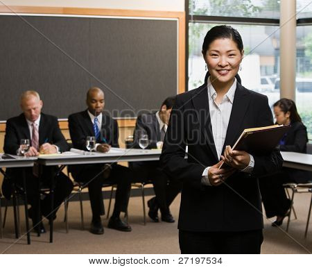 Confident Asian businesswoman standing in front of co-workers in conference room