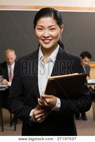 Confident Asian businessman holding files in front of co-workers in conference room poster
