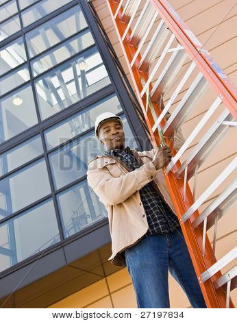 Low angle view of African construction worker lifting ladder