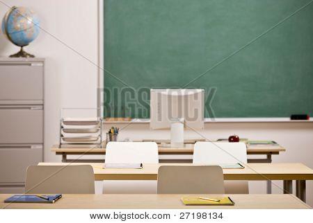 Desks, chairs, blackboard and computer in empty school classroom
