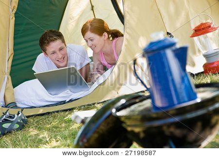 Couple laying in tent with laptop