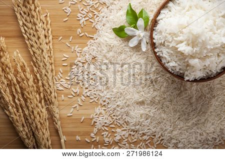 Top View Of Jasmine Rice In A Bowl On Dark Wooden Table With Rice Plants, Jasmine Flower, Ear Of Ric