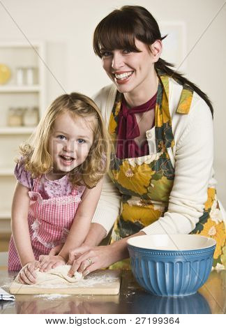 A young child is helping a woman knead some dough to make bread.  They are smiling at the camera.  Vertically framed shot.