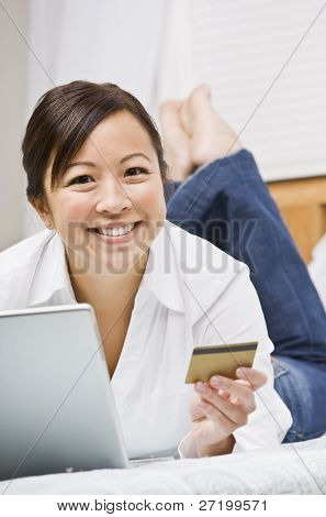Beautiful asian woman holding a credit card and using a laptop.  She is smiling at the camera.  Vertically framed shot.