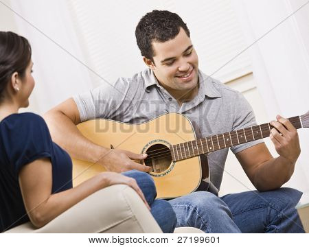 A young and attractive couple sitting on a couch with a guitar.  The male is playing the guitar and the female is watching.  They are smiling.  Horizontally framed shot.