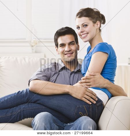 An attractive young couple relaxing together in their home.  The woman is sitting on the man's lap and they are smiling at the camera happily. Square composition.